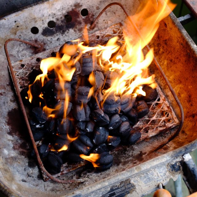 coals on fire getting ready to BBQ